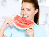 Woman eats a red water-melon — Stock fotografie