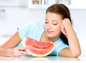 Woman looks at a red water-melon — Stock Photo