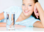 Smiling woman with waters glass — Stock Photo