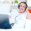 Guy listening music in headphone from laptop — Stock Photo #4083322
