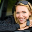 Smiling woman in car with keys — Stockfoto