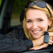 Smiling woman in car with keys - Stok fotoğraf