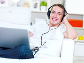 Guy listening music in headphone from laptop — Stock Photo