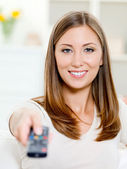 Happy woman with remote control sitting — Stock Photo