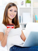 Woman holding credit card with laptop — Stock Photo