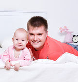 Young father with smiling baby lying — Stock Photo