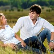 Beautiful couple sitting in meadow — Stock Photo