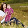 Beautiful mather with smiling beby on nature — Stok fotoğraf