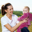 Young mather with smiling child on nature — Foto Stock