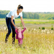 Young mather with smiling beby on nature — Stock Photo