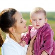 Stock Photo: Beautiful mather with smiling beby on nature