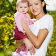 Happy mather with attractive baby outdoor — Stock Photo