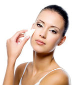 Woman applying foundation on face — Stock Photo