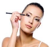 Kvinna tillämpa eyeliner på ögonlocket med pensil — Stockfoto