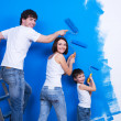 Young family painting the wall — Stok fotoğraf