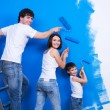 Young family painting the wall - Stock Photo