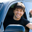 Happy man showing keys in car - Stockfoto
