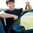 Happy man showing keys near the car — Stock Photo