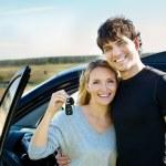 Happy couple near new car — Stock Photo