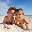 Happy brothers lying on sea beach - Stock Photo