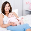 Smiling mother sitting with baby at home — Stock Photo
