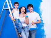 Smiling family with paintbrush — Stock Photo
