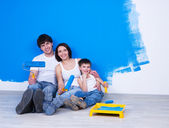 Smiling family with paintbrush near the wall — Stock Photo