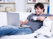 Man with laptop and cup of coffee — Stock Photo