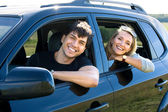 Happy young couple driving the car — Stock Photo