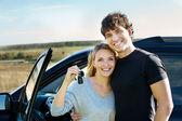 Pareja feliz cerca de coche nuevo — Foto de Stock