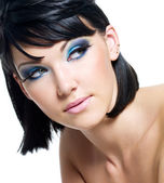 Face of a beautiful woman with blue make-up — Stock Photo