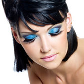 Female face with brightly blue make-up — Stock Photo