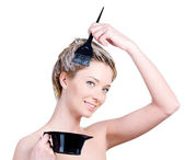 Woman with brush and capacity for hair-dye coloring her hair — Stock Photo