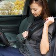 Woman fastens a seat belt in the car — Stok fotoğraf