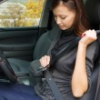 Woman fastens a seat belt in the car — Stock fotografie