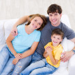 Laughing family with son on the sofa — Stock Photo #4236242