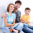 Happy family in casuals on the floor — Stock Photo #4236391
