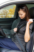 Woman fastens a seat belt in the car — Stock Photo