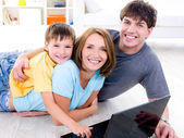 Family with son on the floor with laptop — Stock Photo