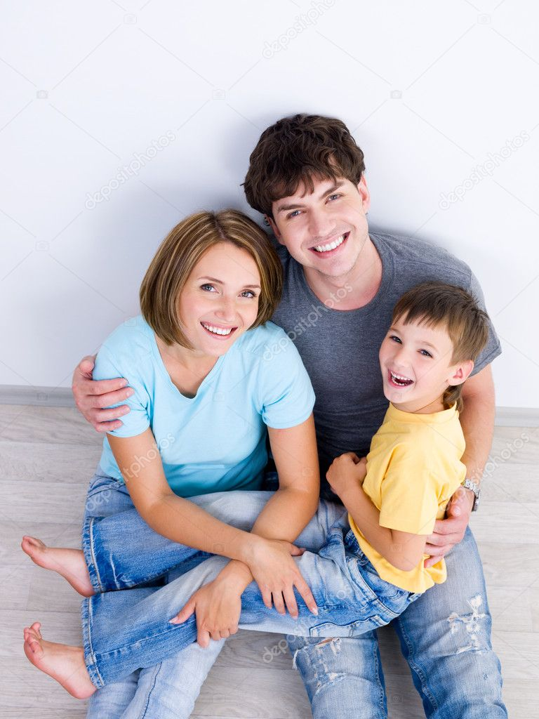 Happy laughing family with young boy sitting on the floor in casuals - high-angle  Stock Photo #4236379