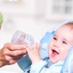 mamma ger vatten till baby — Stockfoto