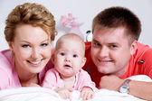 Porträtt av den vackra unga lyckliga familjen — Stockfoto