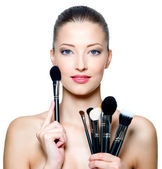 Portrait of the beautiful woman with make-up brushes — Stock Photo