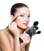 Pretty woman making make-up around the eyes. — Stock Photo