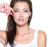 Face of a young woman with cream on face — Stock Photo