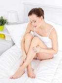 Pretty woman in dedroom touching her beautiful legs — Stock Photo