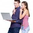 Young beautiful smiling couple looking at laptop — Stock Photo