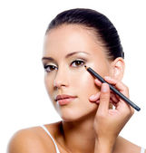 Woman applying eyeliner on eyelid with pensil — Stock Photo