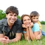 Семья, лежа на зеленой траве — Стоковое фото