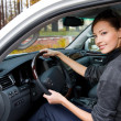 Smiling woman sits in the new car — ストック写真